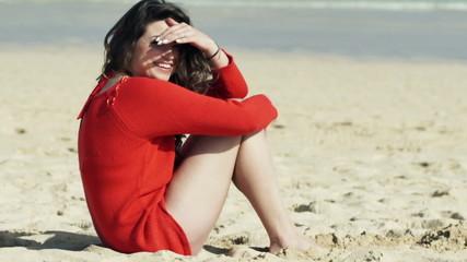 Portrait of happy, flirting woman sitting on beach