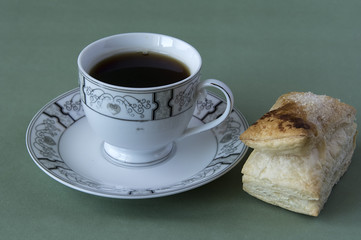Cup of tea on a dish and a puff pastry