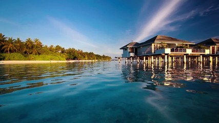 Panning view of the over water villas and tropical island