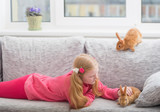 smiling girl  with two rabbits  indoor