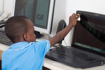 Enfant nettoyant la poussière sur l'écran de l'ordinateur.