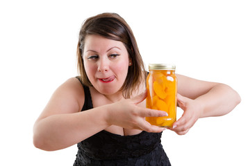 Woman licking her lips and eyeing a mason jar of peaches