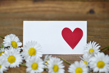 Blank card and daisies on wooden background