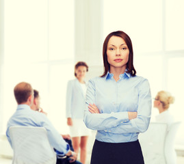 smiling businesswoman with crossed arms at office