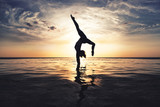 Handstand in the ocean at sunset