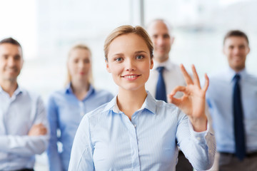 smiling businesswoman showing ok sign in office