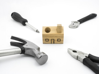 Set of tools and wood house toy on white background