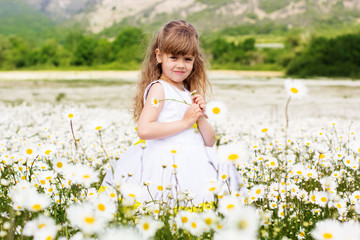 Happy child girl at camomile field