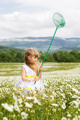 Cute child girl at field of camomiles with net