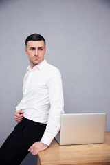 Businessman leaning on the table with laptop
