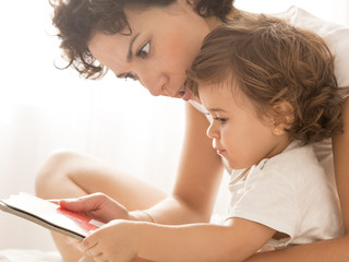 Woman and baby girl reading on bed