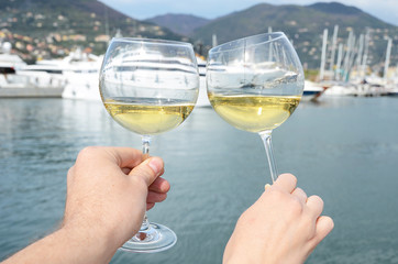Pair of wineglasses in the hands against the yacht pier of La Sp