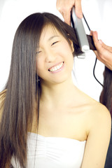 Asian woman getting hair straightened happy