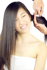 Cute asian girl with long hair getting combed by stylist