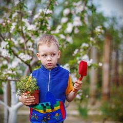 Handsome little blond boy planting and gardening flowers in gard