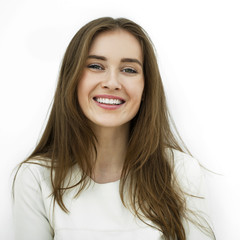 Beautiful young happy woman posing against a white wall