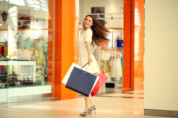 Beautiful young woman holding shopping bags walking in the shop