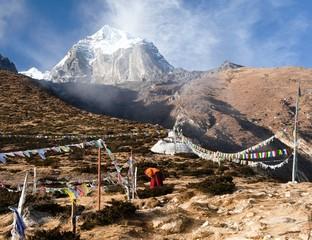 Buddhist monk, stupa and prayer flags near Pangboche