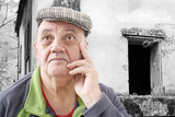 Maison délaissée en ruine avec vieil homme songeur
