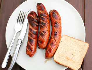 Barbeque sausages on wooden table