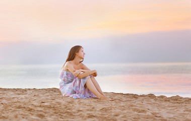 Young woman sitting on the beach at coast enjoying sea sunset