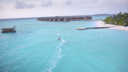 Aerial view of the surfer enjoying at beautiful Maldives