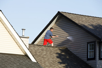 Man on the roof of a house pressure washing the vinyl siding.
