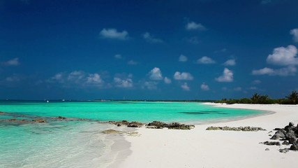 Tropical beach in Maldives with crystal clear water and rocks