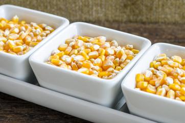 Golden corn grain in the bowl. Shallow depth of field.