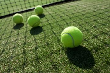tennis balls on tennis grass court