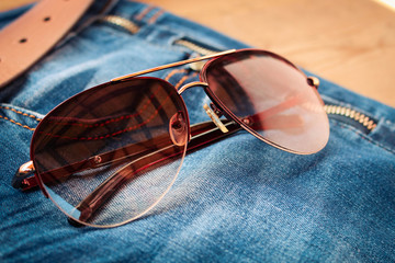 Sunglasses on jeans background. Toned image.