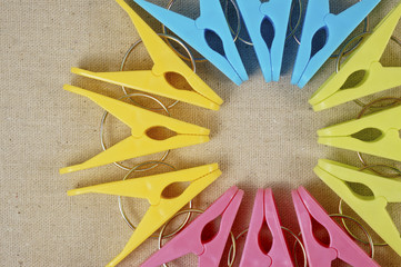 Colorful clothespins in a circle on fabric background