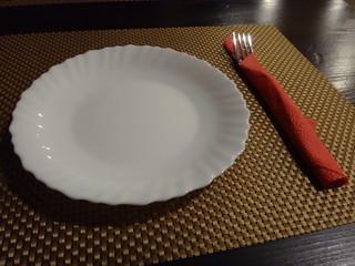 Белая тарелка с витым краем и вилка в красной салфетке