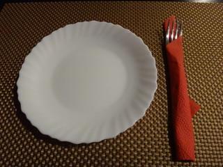 Белая тарелка и вилка в красной салфетке