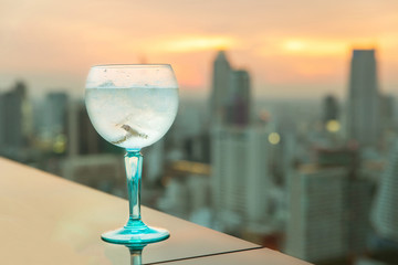 Gin tonic cocktail on table in rooftop bar