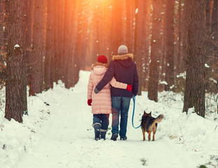 Young happy couple with dog walking in the winter forest