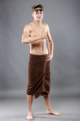 Young attractive caucasian man swimmer with goggles and towel is