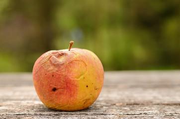 Rotten apple on wooden table