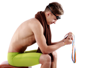 swimmer sits and looks at medal