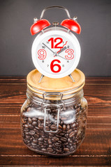 Coffee time,alarm clock with white coffee cup and coffee bean in