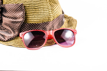 Red sunglasses and beach hat isolated on white background