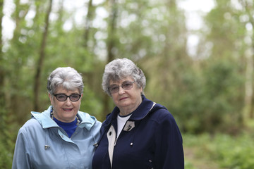 Elderly twin sisters walking in the woods