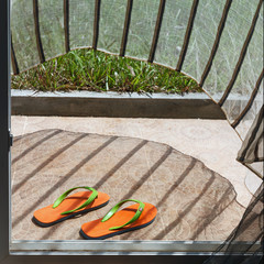 Orange flip-flops lying at a house entry