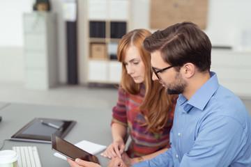zwei mitarbeiter schauen zusammen auf tablet-pc