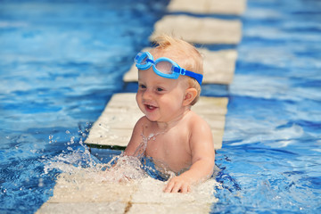 Happy child playing with water splashes in pool before