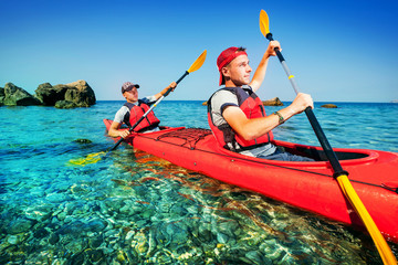 Two men paddle a kayak on the sea. Kayaking on island.