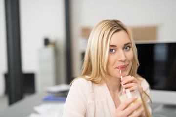 junge frau trinkt einen gesunden saft am arbeitsplatz