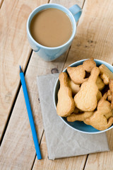 Sweet tasty cookies in the blue plate, a cup of coffee with milk