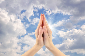 Two praying hands facing the sky