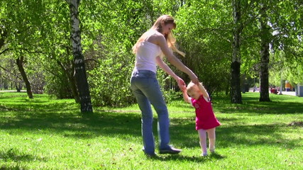 The young woman walks with the little girl in park
